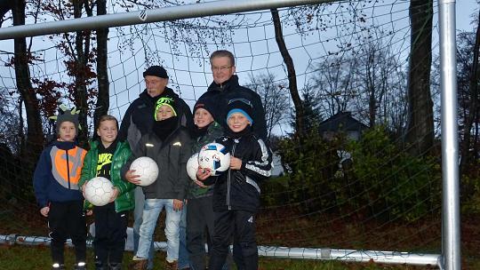 Da freuen sich die Kids mit Norbert Brewer (hinten links) und Erwin Finken vom Senioren-Arbeitsteam der Hansa: Der Bolzplatz am Ende der Simrodstraße hat zwei neue Tore bekommen. Foto: Karl-Heinz Hoffmann